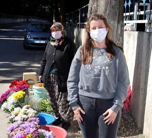 Merve Bozkurt đứng cạnh mẹ - khi bán hoa ở cổng nghĩa trang trong phóng sự của truyền hình địa phương. Ảnh: Rasim Burunç.