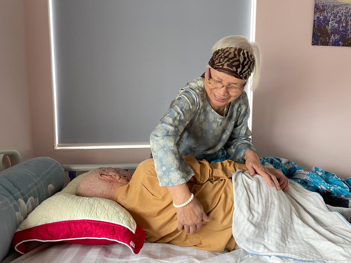 Bà Dành luôn muốn được tự tay chăm sóc cụ ông. Chỉ những việc không làm được bà mới cần nhân viên giúp đỡ. Ảnh: Phan Dương.
