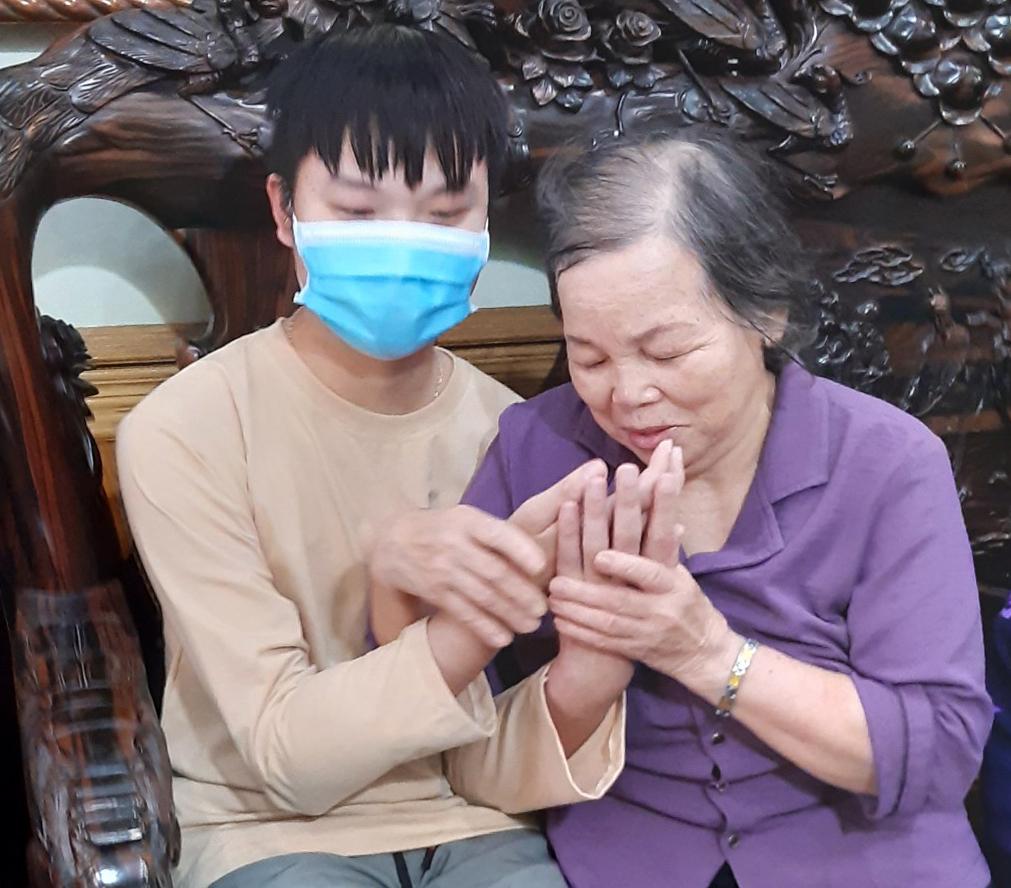 Bà Nhường lầu đầu tiên gặp cậu bé nhận hai tay của con. Ảnh: Gia đình cung cấp.