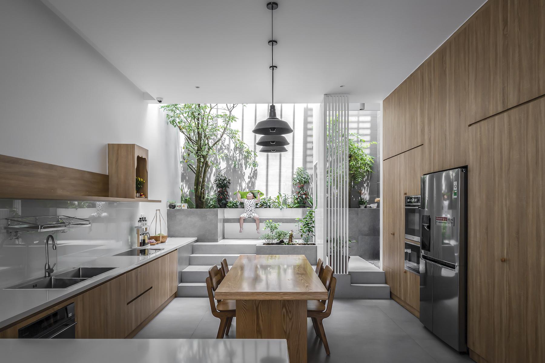 Khu bếp và phòng ăn nhìn ra sân sau với cây xanh và giếng trời.