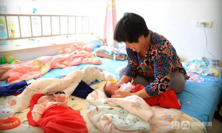 Trương Ngọc Mai chăm sóc cặp song sinh được hơn 1 tháng tuổi của mình tại nhà riêng ở thành phố Yên Đài, tỉnh Sơn Đông, Trung Quốc. Ảnh: 163.com