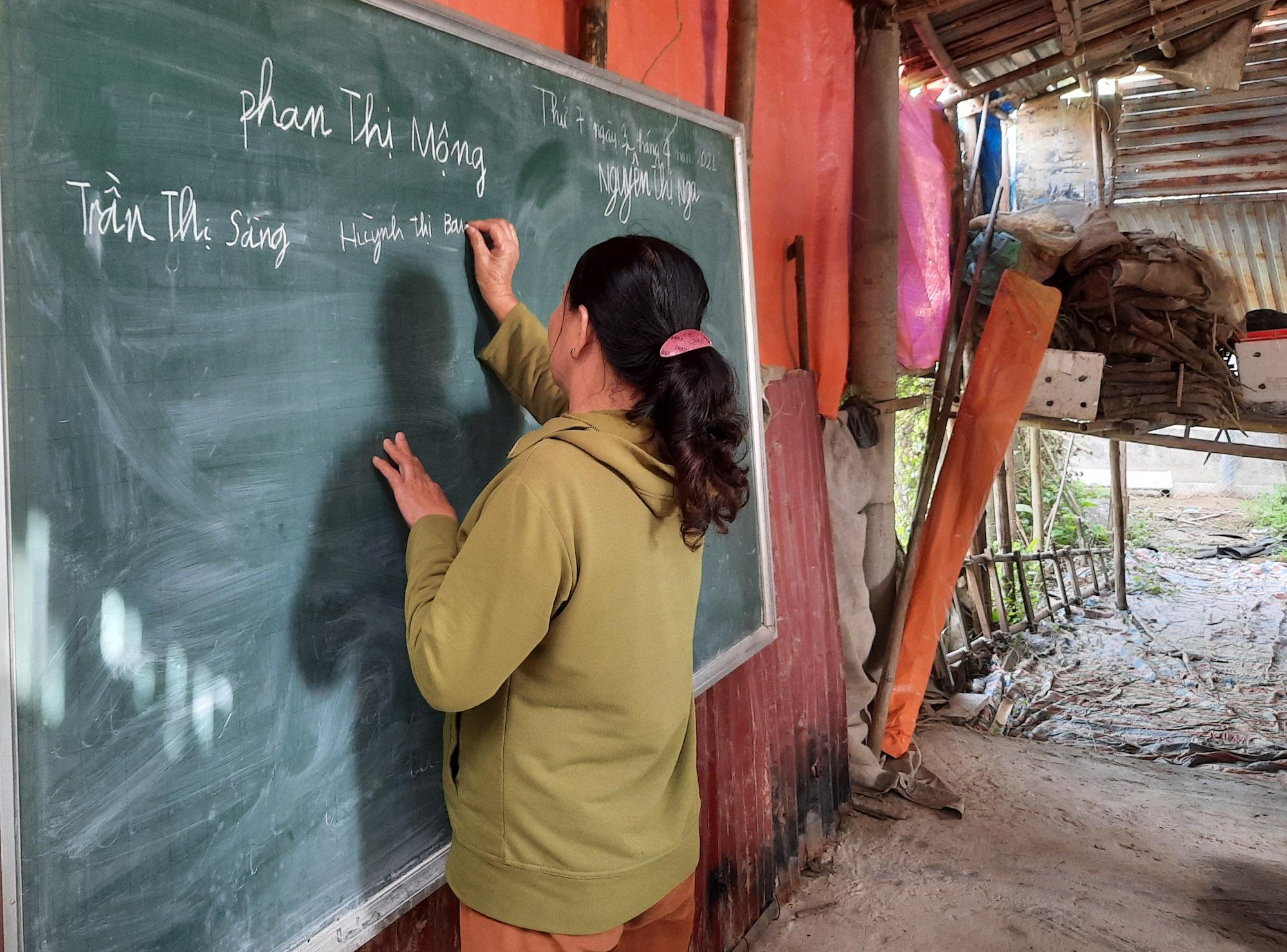 Học viên lớp xóa mù chữ lên bảng viết tên mình. Ảnh: Diệp Phan.