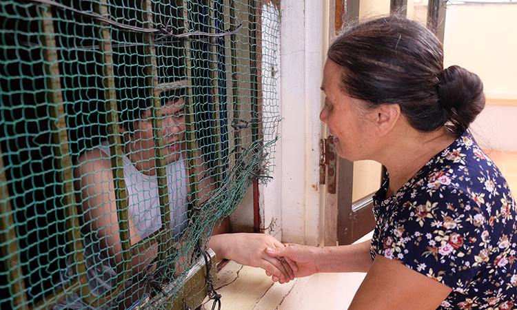 Bà Ngô Thị Nam thường xuyên dỗ dành con trai để anh không đập đầu vào tường, gây hại cho mình. Anh Cường, con bà Nam bị tâm thần 16 năm trước sau vụ tai nạn giao thông dẫn đến dập não. Ảnh: Hải Hiền.