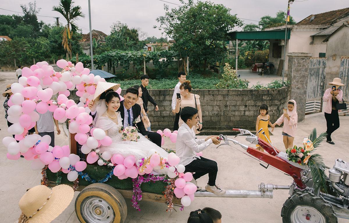 Anh Hân và chị Mai (ngồi phía sau máy cày) tại lễ rước dâu, trưa 22/4. Ảnh: Vương Quyền