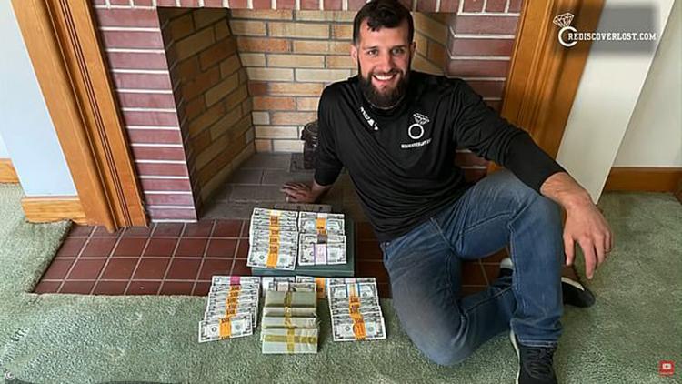 Keith Wille cùng hộp tiền được tìm thấy trên gác mái. Ảnh: Keith Wille/YouTube