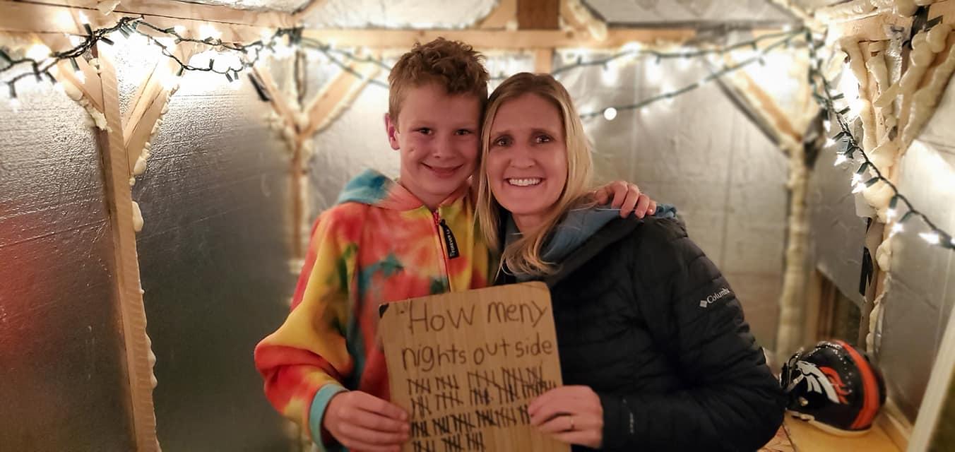 Cậu bé và mẹ với tấm bảng 100 đêm ngủ một mình ở cabin. Ảnh: Thepochtimes.