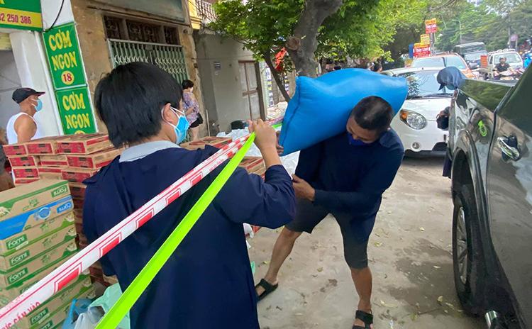 Thực phẩm được tập kết tại hàng rào phong tỏa trước ngõ 91 của tổ dân phố 14 trước khi giao đến các bệnh nhân ung thư ngoại trú của viện K Tân Triều. Ảnh: Đỗ Ngọc.