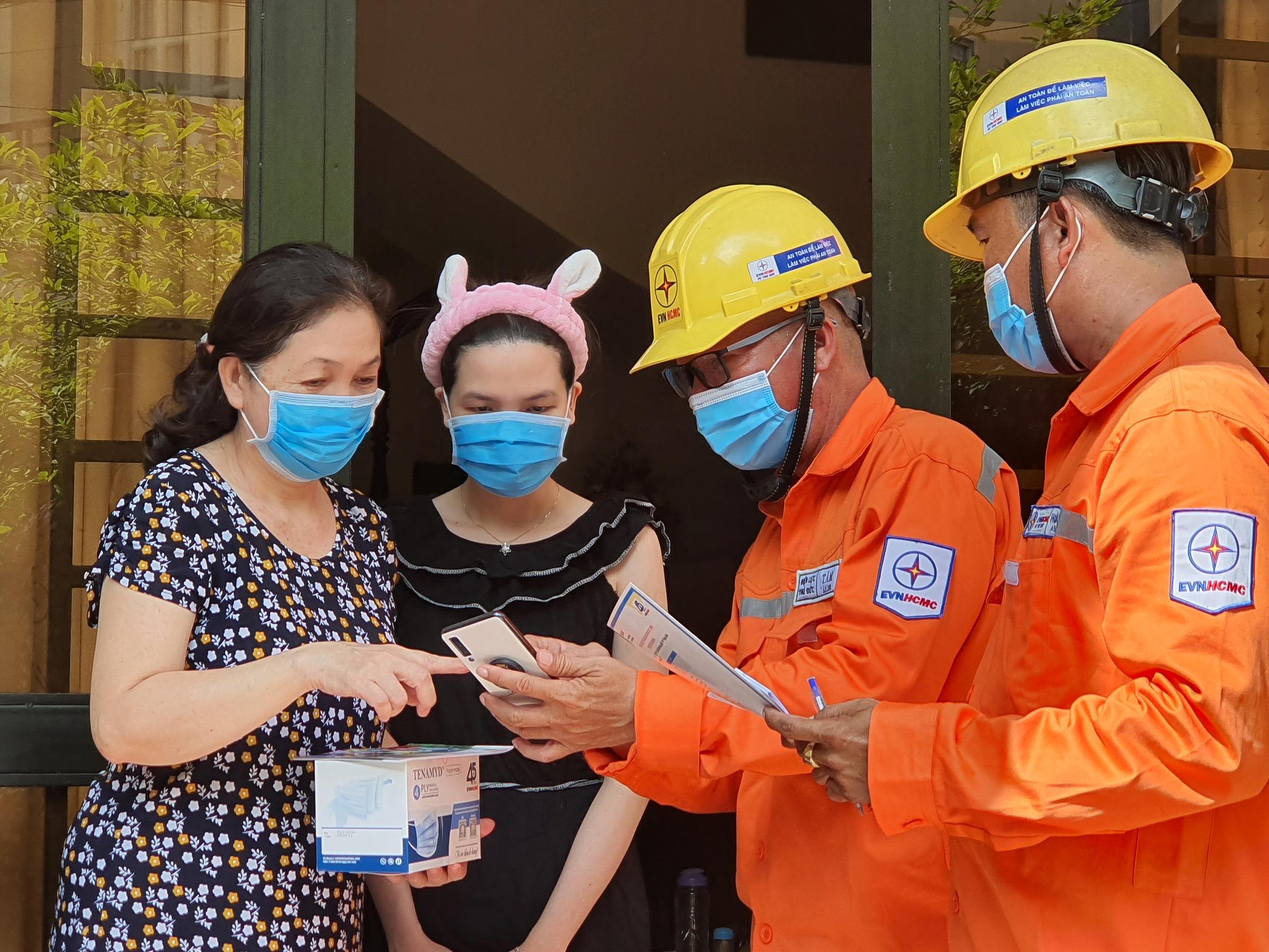 Nhân viên Điện lực TP HCM hướng dẫn cài đặt ứng dụng tại nhà cho các hộ dân. Ảnh: EVNHCMC.