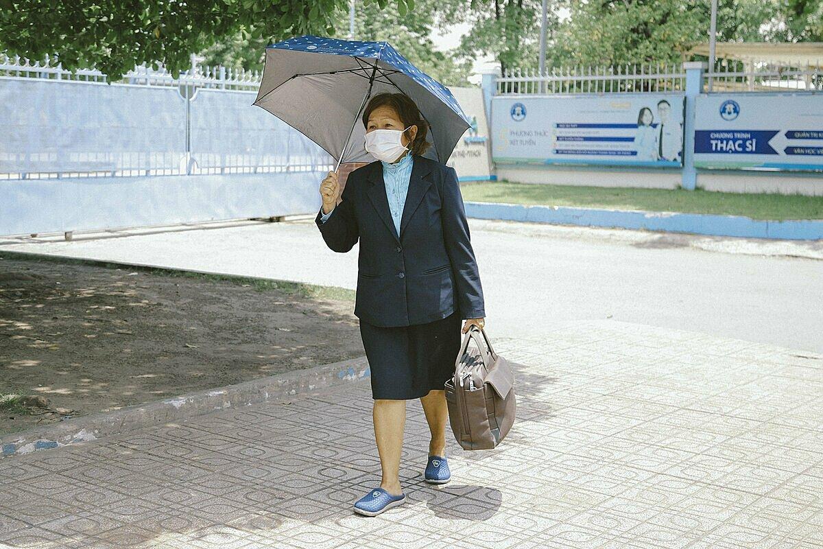 Hành trang mỗi buổi đến lớp của bà Hoàng luôn có cặp xách nặng trĩu và chiếc dù che nắng, mưa. Ảnh: Trường đại học Văn Hiến.