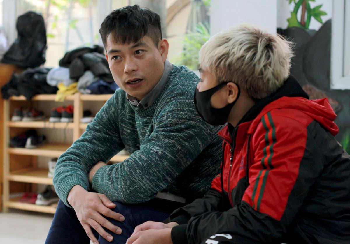 Anh Vị trò chuyện với một trẻ, thuyết phục em tham gia một giải chạy ở Mộc Châu cuối tháng 1, với hy vọng thông qua các hoạt động này, đứa trẻ hòa nhập lại cuộc sống bình thường, từ đó tăng tự tin về bản thân. Ảnh: Phan Dương.