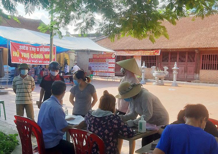 Các chủ trọ ký tên trước khi nhận nhu yếu phẩm cho công nhân tại đình làng, thuộc tổ dân phố My Điền 1, thị trấn Nếnh, Việt Yên, Bắc Giang. Ảnh: Lê Minh Thống.