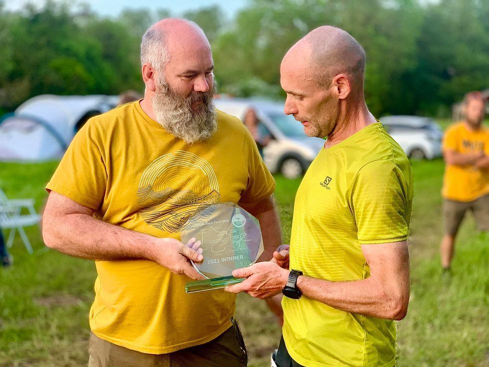 John nhận cup từ đại diện Ban tổ chức giải. Ảnh: Challenge Running.