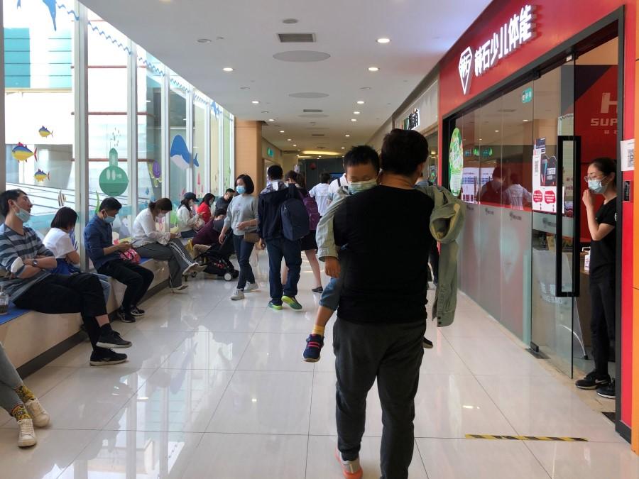 Một ông bố bế con vào lớp học năng khiếu, trong khi nhiều phụ huynh khác đang chờ con bên ngoài tại Hoàng Trang, Hải Điến. Ảnh: Thinkchina.