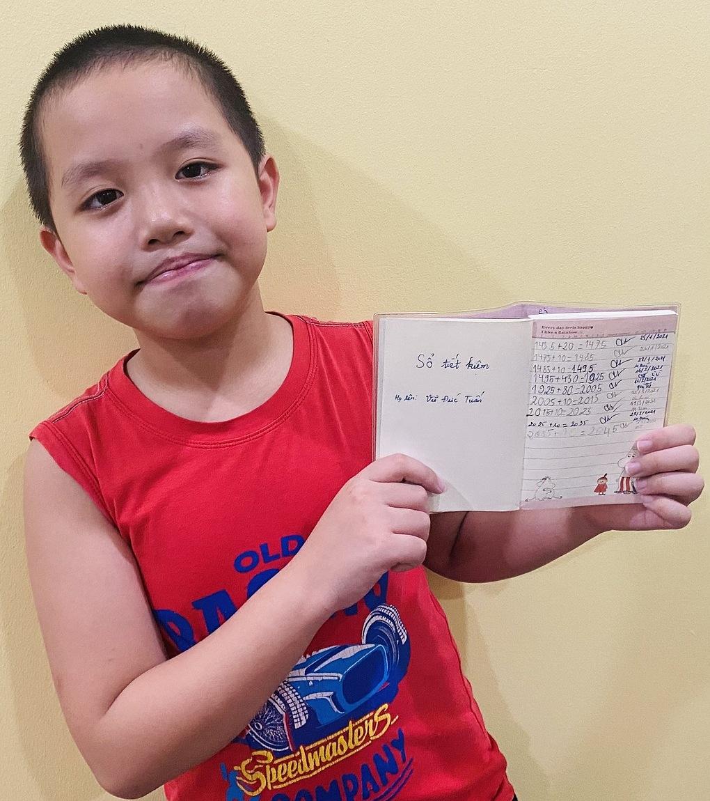 Bé Đức Tuấn, một nhân vật tham gia cuộc thi Cha-Ching - Bé giỏi tiền hay được mẹ hướng dẫn ghi sổ tiết kiệm tại nhà. Ảnh: NVCC