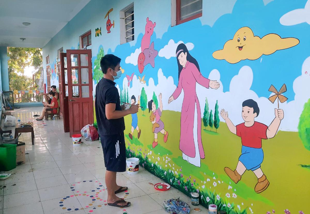 AnhLợi (áo đen) đang hoàn thiện một bức bích họa ở trường Mầm non Sơn Trung. Ảnh: Hùng Lê