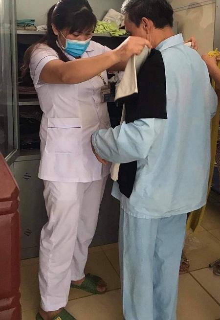 Nhân viên y tế ướm quần áo cho bệnh nhân, từ tủ quần áo từ thiện do Phạm Mai Hương gửi tặng. Ảnh: Nhân vật cung cấp.