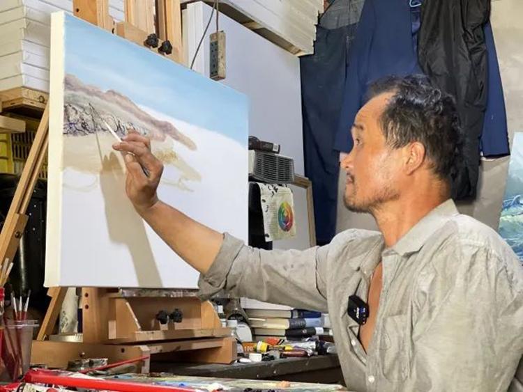 Lập Quang Minh vẽ tranh trong phòng thuê vỏn vẹn 15m2. Ảnh: Huanqiu.