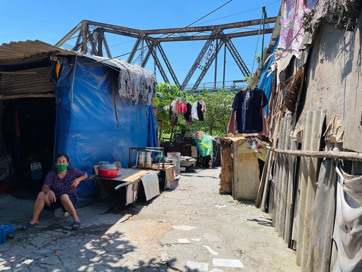Bà Lĩnh ngồi mé hiên hàng xóm lúc 11h trưa ngày 18/6 trong xóm ổ chuột dưới chân cầu Long Biên. Nhà của bà là căn quây tôn bên phải. Ảnh: Phan Dương.
