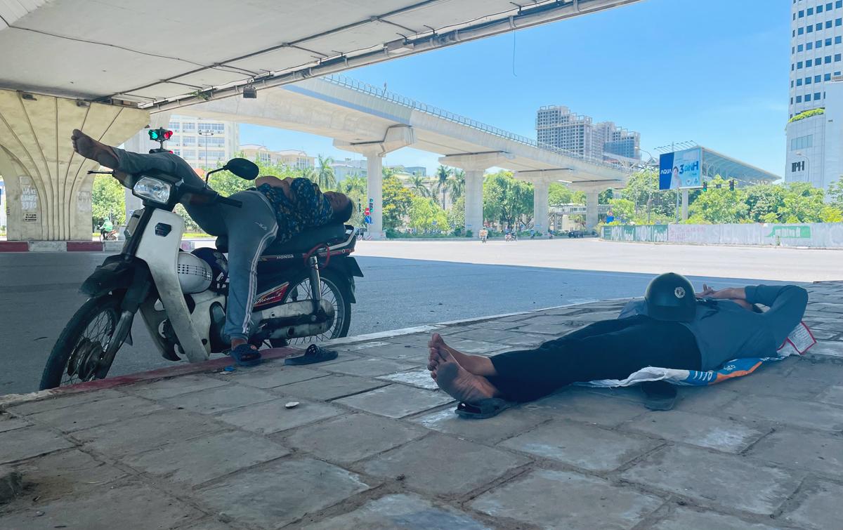 Người lao động chợp mắt trưa 19/6, ngày khi nhận nắng nóng gay gắt, nhiệt độ mặt đường có thể lên tới 50 độ C. Ảnh: Phan Dương.