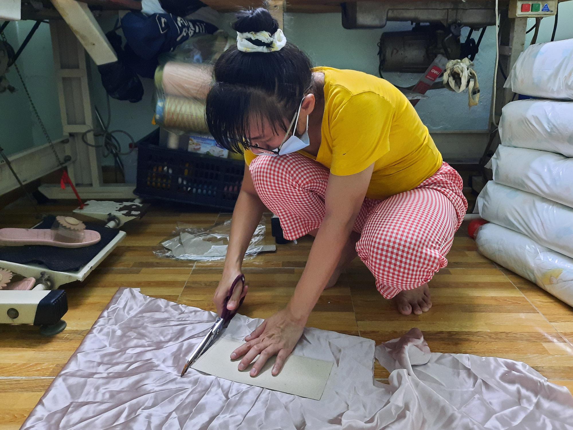 Chị Hà vừa được một người dân ở quận Gò Vấp gửi vải đến để chị ra rập, may mẫu quần áo. Ảnh: Diệp Phan.