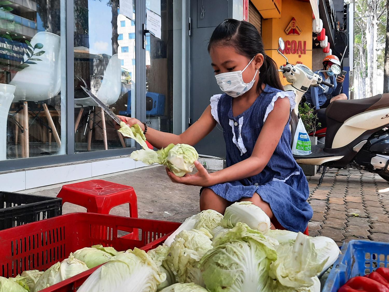 Bé Quỳnh Như đang phụ sơ chế bắp cải trước quán ăn Mãn Tự, trưa ngày 29/6. Ảnh: Diệp Phan.
