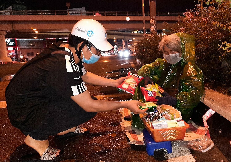 Trường Thành đang tặng phần ăn cho bà Quế, 70 tuổi ở góc đường Ngã 5 Chuồng Chó tối 5/7. Ảnh: Diệp Phan.