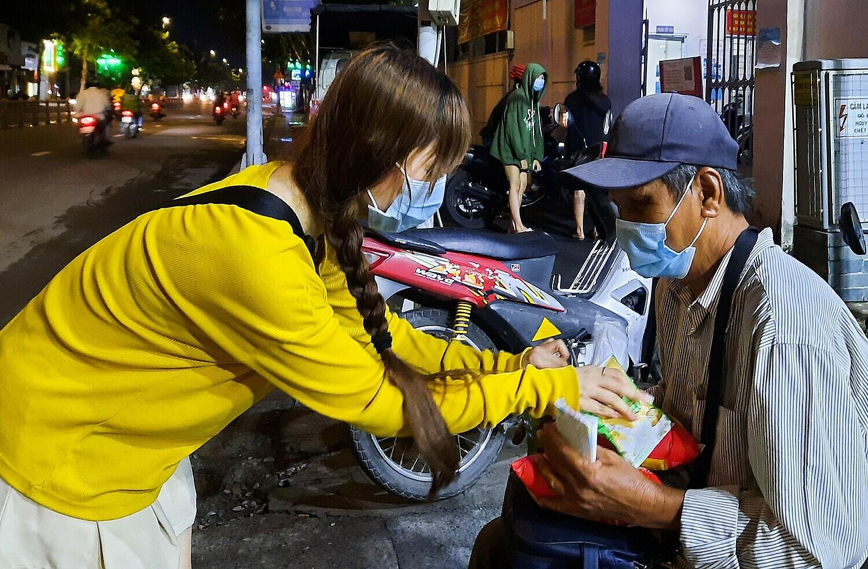 Mai Hiền, 29 tuổi đã quay lại để tặng phần ăn cho ông Hòa khi ông đang ngồi bán trước một cây xăng trên đường Quang Trung đêm 5/7. Ảnh: Diệp Phan.