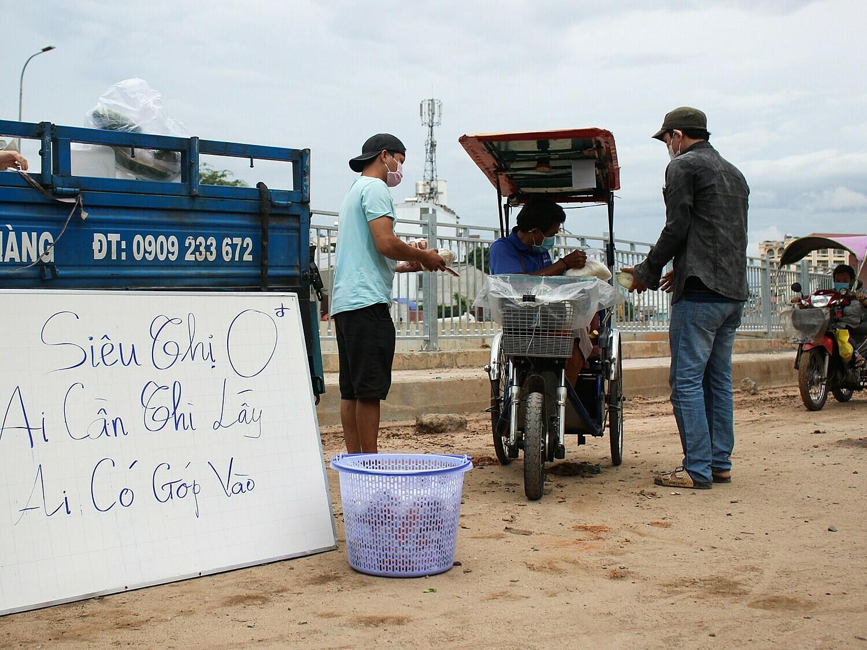 Anh Hưng (áo đen) gửi thực phẩm tặng những người khuyết tật bán vé số trong con hẻm đường Tân Kỳ Tân Quý, quận Tân Phú chiều ngày 7/7. Ảnh: Diệp Phan.