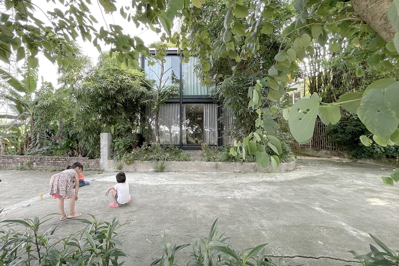 Nhìn từ bên ngoài, ngôi nhà lấp ló giữa hàng cây.