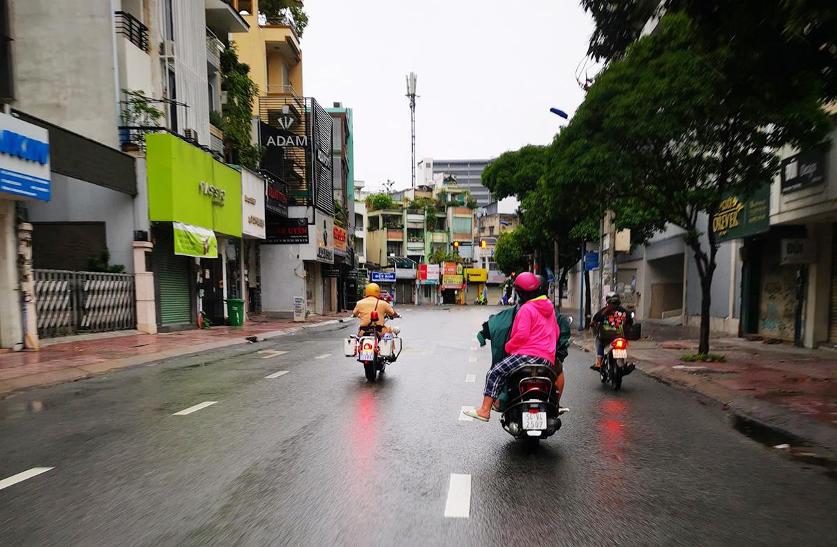 Thượng úy Nguyễn Văn Hùng dẫn đường cho cặp vợ chồng (áo hồng, xe biển số 54V4 -2507) trên đường Hồ Văn Huê. Suốt đường đi, anh cũng điều tiết xe ở các ngã ba, ngã tư để cặp vợ chồng di chuyển an toàn. Ảnh: Qua Nguyễn