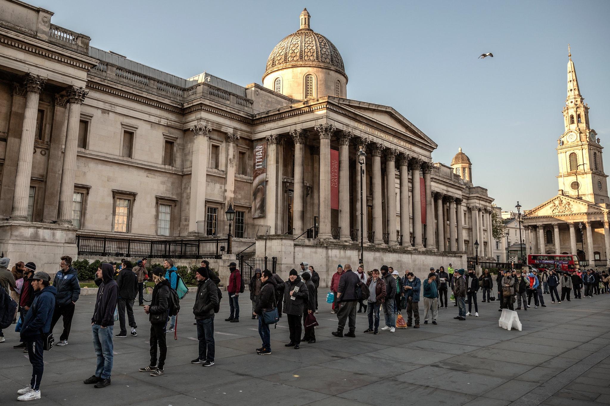 Những người vô gia cư và người khác xếp hàng nhận đồ ăn miễn phí tại Quảng trường Trafalgar ở London tháng 4/2020. Ảnh: Nytimes.