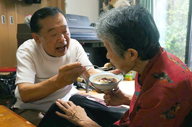 Người chồng dỗ vợ ăn như em bé. Ảnh: Asahi