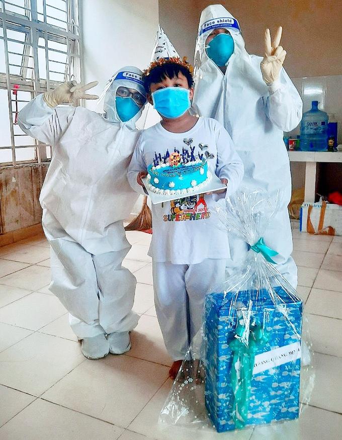 Bác sĩ Đức Mạnh và điều dưỡng Châu thay mặt tất cả những người yêu thương tặng quà sinh nhật cho cậu bé F0 Ken, 9 tuổi, ngày 5/8. Ảnh: Bệnh viện Nhi đồng thành phố