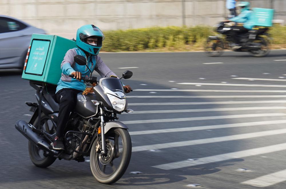 Một tài xế giao hàng cho ứng dụng Deliveroo phóng nhanh qua một bùng binh ở Dubai, ngày 9/9. Ảnh: AP