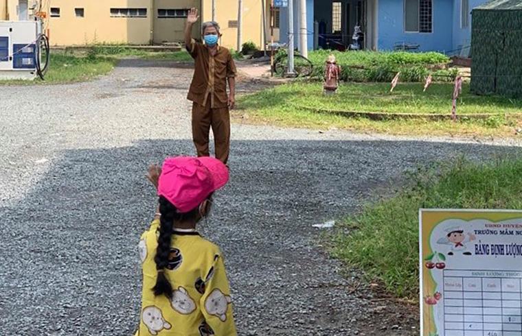 Cô bé mồ côi 7 tuổi này bịn rịn chia tay ông ngoại để về quê Long An nương nhờ họ hàng, hôm 17/8. Ảnh: Bệnh viện Nhi đồng thành phố.