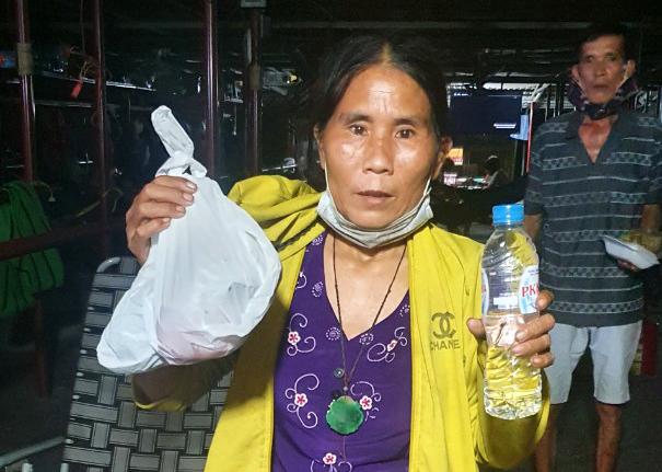Bà Hà cũng như những người lao động tự do khác trong quán võng chia nhau đồ ăn xin được, tối 18/9. Ba tháng qua, nhóm người ở đây sống chủ yếu bằng đồ cứu trợ san sẻ với nhau. Ảnh: Hòa Nguyễn