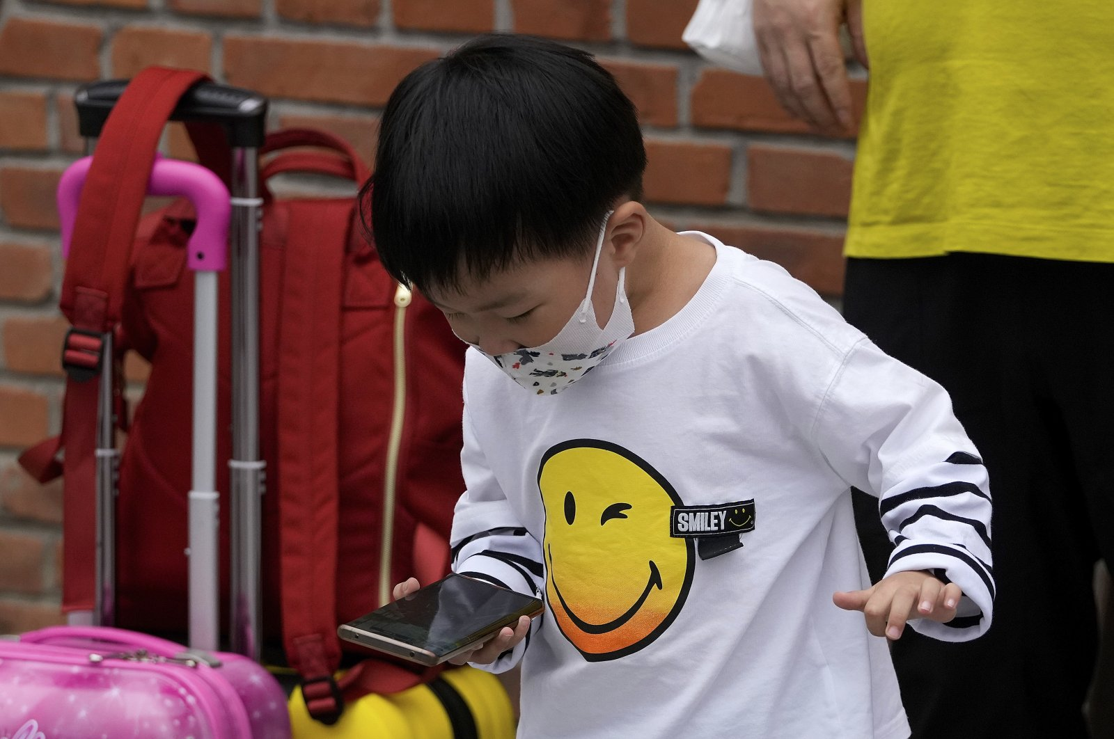 Một đứa trẻ chơi game bên cạnh người thân trên một con phố ở Bắc Kinh, ngày 12/9/2021. Ảnh: AP