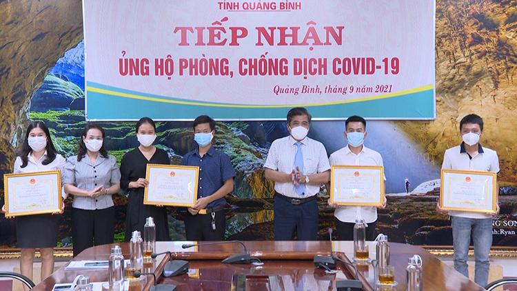 Hai vợ chồng Hương, Nghĩa (áo đen, xanh) trong buổi nhận bằng khen của tỉnh Quảng Bình vì có đóng góp trong phòng chống Covid/19, ngày 23/9. Ảnh: Nhân vật cung cấp.