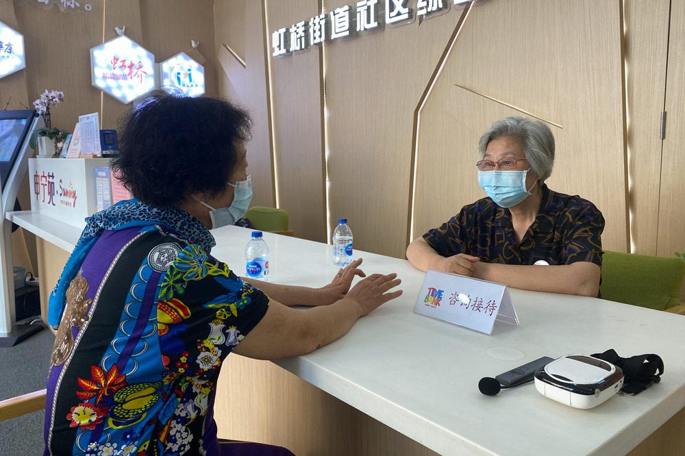 Chen Wenhua trả lời các câu hỏi của một cư dân địa phương khi làm lễ tân ở trung tâm người cao tuổi Hồng Kiều, ngày 19/8. Ảnh: Sixthtone