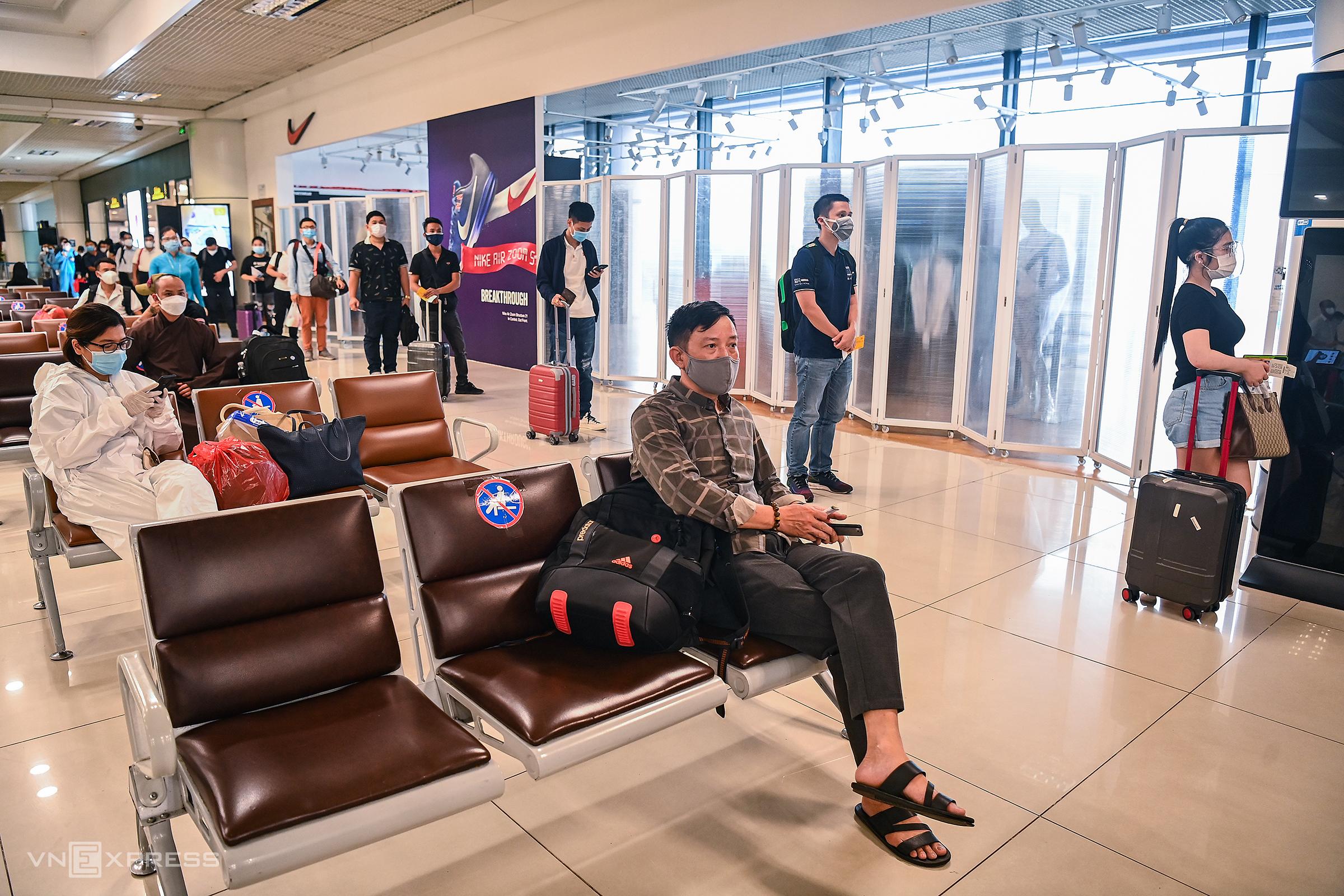 Hành khách ngồi và đứng giãn cách trước giờ lên chuyến bay thương mại đầu tiên VN213 đi TP HCM. Ảnh: Giang Huy
